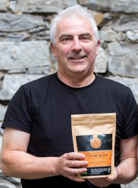 Photo of director John Brennan holding a pack of Blakes coffee beans